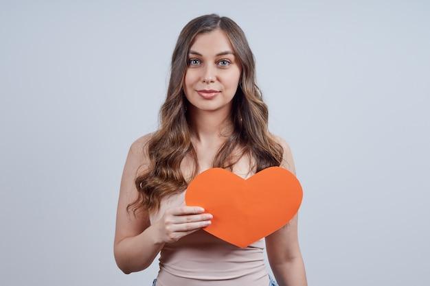 Mooie vrouw met een hart van papier op haar borst, kijkend naar de camera, op een grijze achtergrond. fijne valentijnsdag. wereldhartdag.