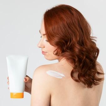 Mooie vrouw met een huidverzorgingsproduct