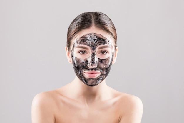 Mooie vrouw met een klei of een moddermasker op haar gezicht dat over witte muur wordt geïsoleerd