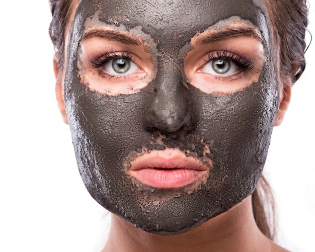 Mooie vrouw met een klei of een moddermasker op haar gezicht