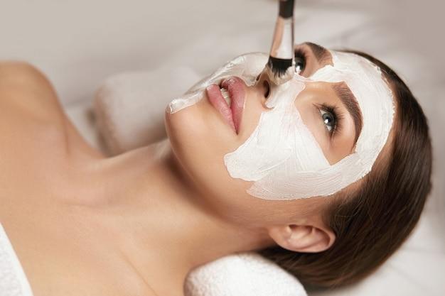 Mooie vrouw met een kleimasker op haar gezicht. masker voor gezichtspeeling. spa huid- en lichaamsverzorging. vrouwelijke gezichtsbehandeling van schoonheidsbehandeling. cosmetologie.