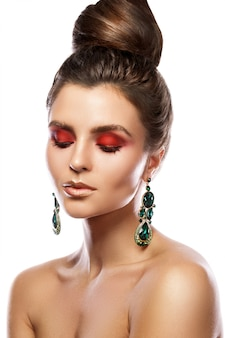 Mooie vrouw met een kleurrijke make-up draagt oorbellen met groene smaragden