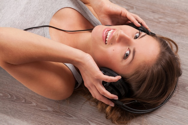 Mooie vrouw met een koptelefoon op de vloer liggen