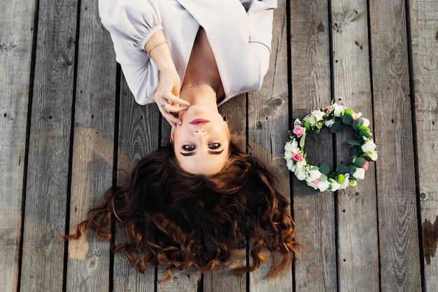 Mooie vrouw met een krans op een houten vloer