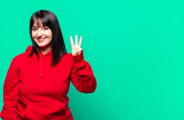 Mooie vrouw met een maatje meer die lacht en er vriendelijk uitziet, nummer drie of derde toont met de hand naar voren, aftellend