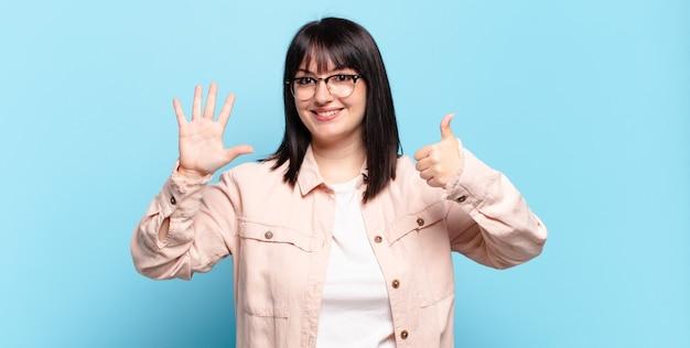Mooie vrouw met een maatje meer die lacht en er vriendelijk uitziet, nummer zes of zesde toont met de hand naar voren, aftellend