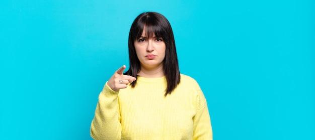 Mooie vrouw met een maatje meer die naar de camera wijst met een boze agressieve uitdrukking die eruitziet als een woedende, gekke baas