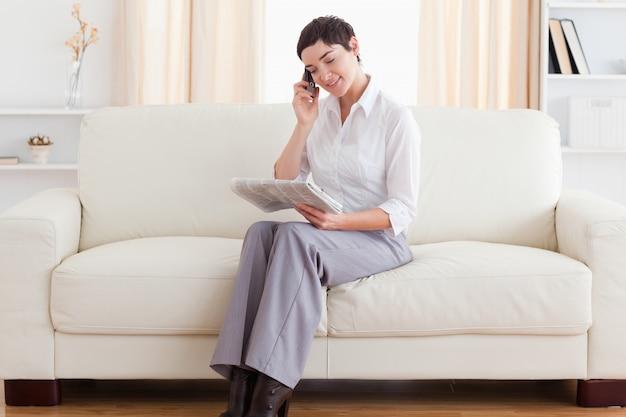 Mooie vrouw met een mobiel en een krant