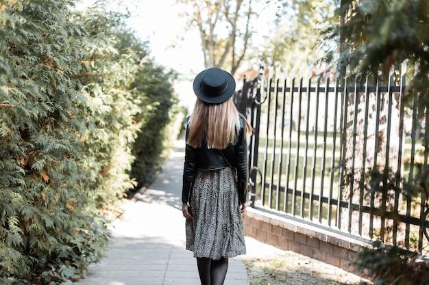 Mooie vrouw met een modieuze zwarte hoed in een leren jas met een jurk loopt in het park op een zonnige herfstdag, achteraanzicht