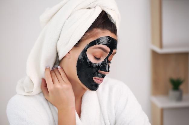 Mooie vrouw met een reinigend zwart masker op haar gezicht