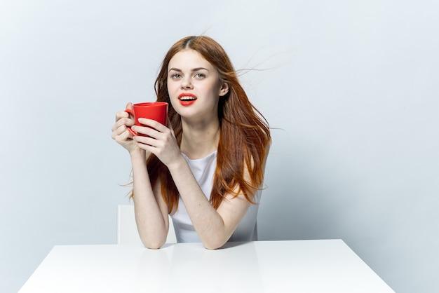 Mooie vrouw met een rode mok in haar hand zittend aan tafel koffie