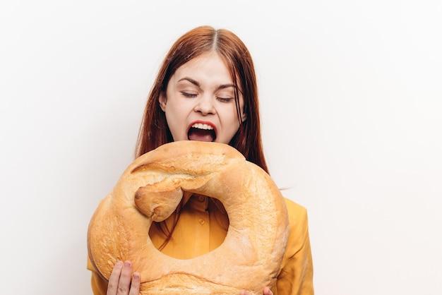 Mooie vrouw met een rond brood in haar handen en opende haar mond wijd