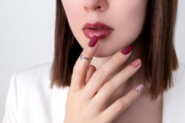 Mooie vrouw met een roze manicure in minimalistische stijl met sieraden