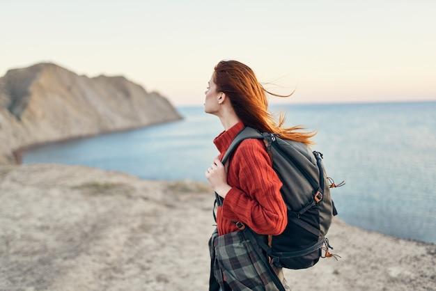 Mooie vrouw met een rugzak in de oceaanzee van het het modelkapsel van de bergen rode sweater
