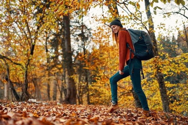 Mooie vrouw met een rugzak in het park op de gevallen bladeren van het aardlandschap