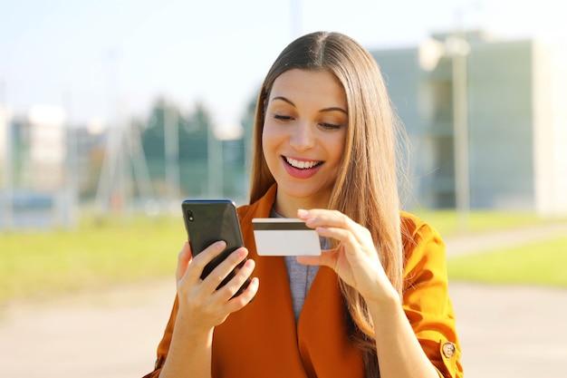 Mooie vrouw met een smartphone en een creditcard