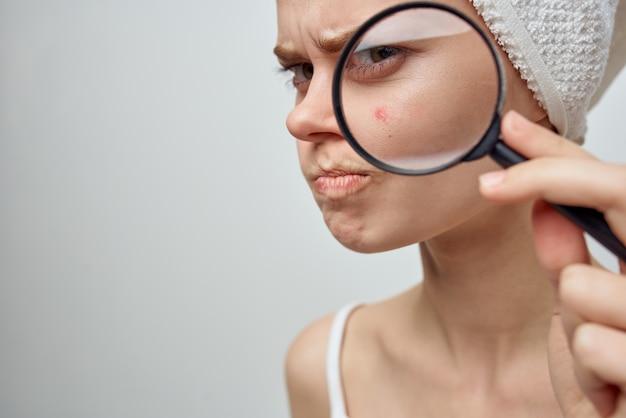Mooie vrouw met een vergrootglas in de hand huidproblemen close-up