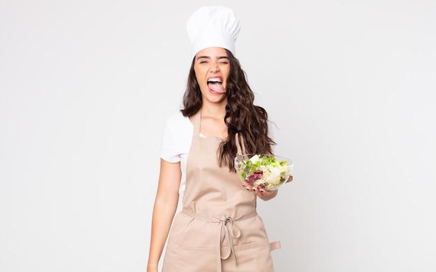 Mooie vrouw met een vrolijke en opstandige houding, een grapje en tong uitsteekt die een schort draagt en een salade vasthoudt