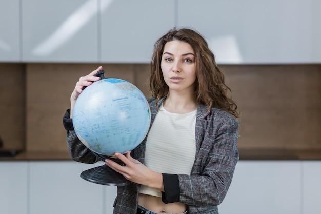 Mooie vrouw met een wereldbol in haar handen, en glimlachen, is in het kantoor