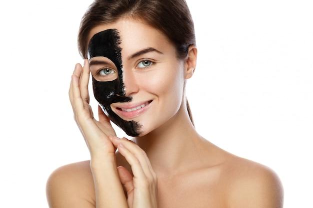 Mooie vrouw met een zuiverend zwart masker op haar gezicht