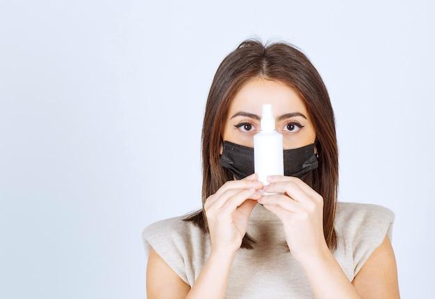 Mooie vrouw met een zwart medisch masker met een spray.
