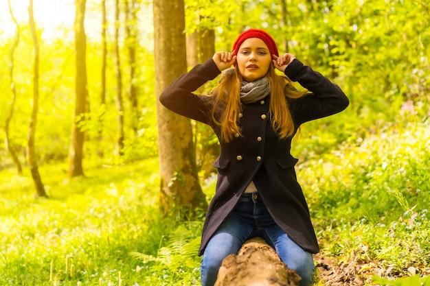 Mooie vrouw met een zwarte jas en een rode hoed die geniet in een herfstpark, zittend op een boom en naar de camera kijkt