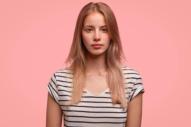 Mooie vrouw met ernstige uitdrukking, gezonde huid, licht haar, gekleed in een gestreept t-shirt, poseert over roze muur heeft een aantrekkelijk uiterlijk