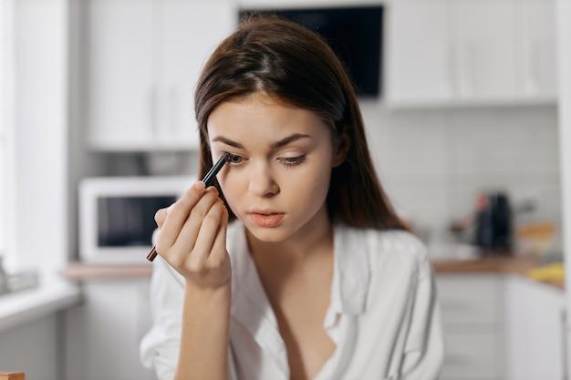 Mooie vrouw met eyeliner potlood make-up cosmetologie kamer keuken