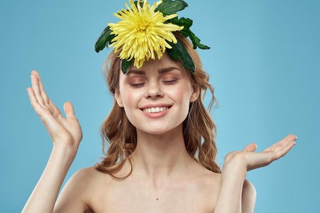 Mooie vrouw met gele bloem dichtbij gezicht het glimlachen bijgesneden meningsportret van kale schouders