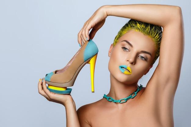 Mooie vrouw met gele holdings kleurrijke schoenen