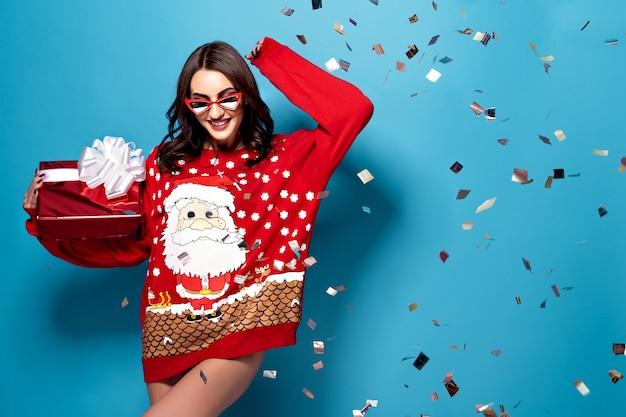 Mooie vrouw met geschenkdoos staande onder vallende confetti