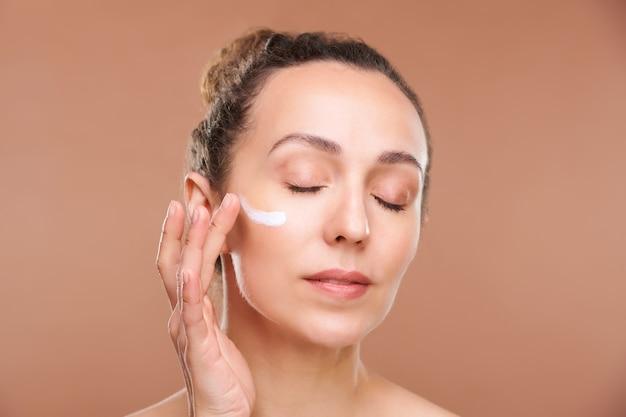 Mooie vrouw met gesloten ogen crème toe te passen op het gebied van haar gezicht onder de ogen, terwijl het verzorgen van de huid na ochtendhygiëne in isolatie