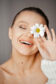 Mooie vrouw met gesloten ogen in een witte trui brengt een witte bloem voor haar oog