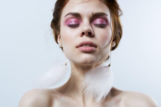 Mooie vrouw met gesloten ogen pluizige oorbellen cosmetica luxe sieraden