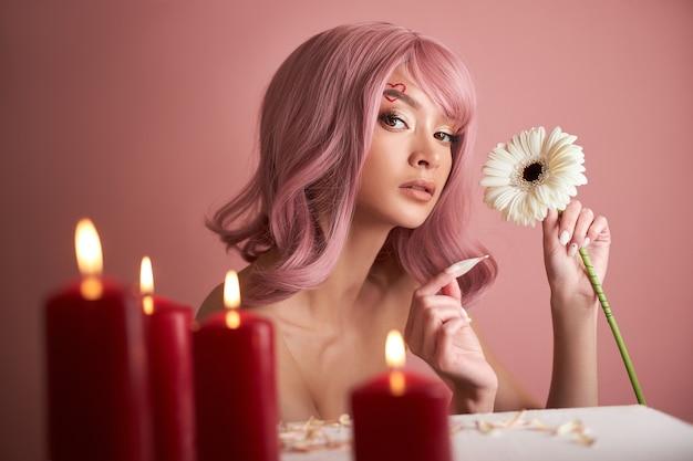 Mooie vrouw met geverfd roze haar bloem in de hand gissen aan tafel met kaarsen. roze schoonheidshaar op het hoofd van de waarzegster van de vrouw