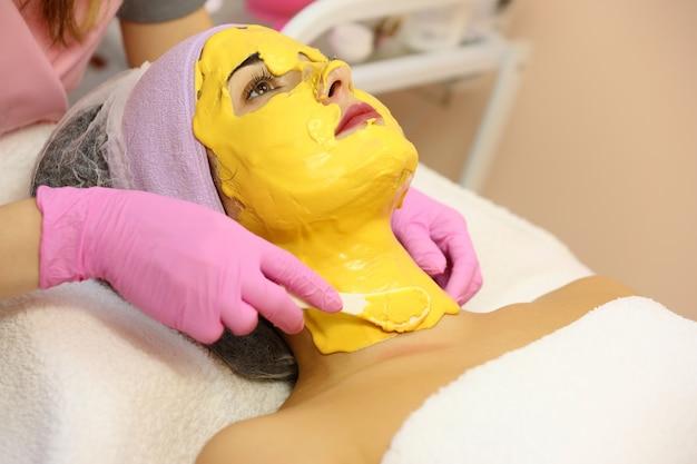 Mooie vrouw met gezichtsmasker bij schoonheidssalon.