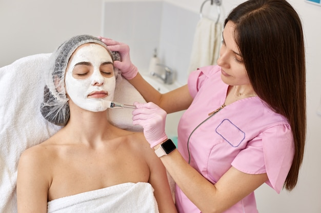 Mooie vrouw met gezichtsmasker die met gesloten ogen op couh bij schoonheidssalon liggen. cosmetologist draagt roze medische jurk