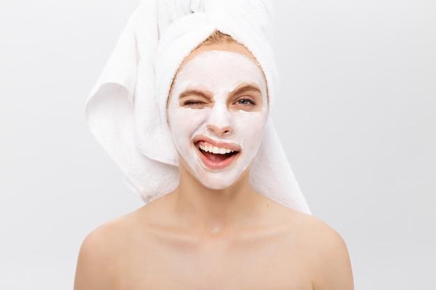Mooie vrouw met gezichtsmasker op witte achtergrond