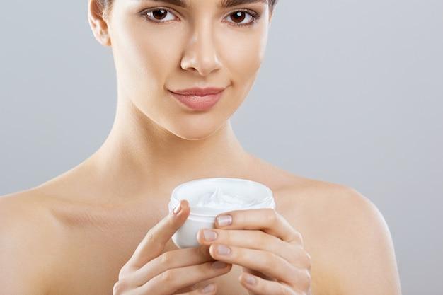 Mooie vrouw met gezichtsroom. bescherming van de huid. huidsverzorging. spa. een jonge vrouw houdt vochtinbrengende crème en lacht