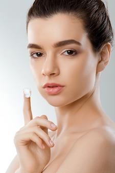 Mooie vrouw met gezichtsroom. bescherming van de huid. huidsverzorging. spa.