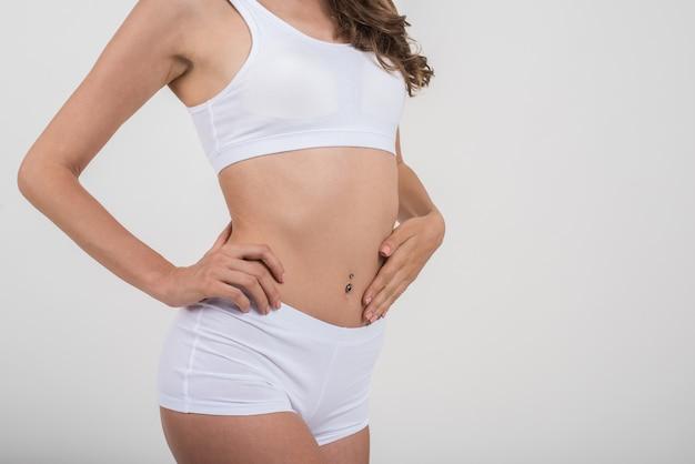 Mooie vrouw met gezond lichaam op witte achtergrond