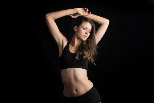 Mooie vrouw met gezond lichaam op zwarte achtergrond