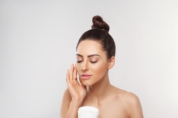 Mooie vrouw met gezonde gladde gezichts schone huid fles cosmetische crème te houden