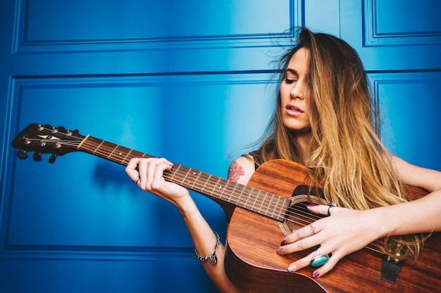 Mooie vrouw met gitaar dichtbij blauwe muur