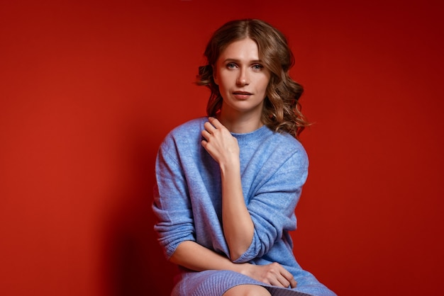 Mooie vrouw met golvend haar in een blauwe trui die zich voordeed op een rode muur