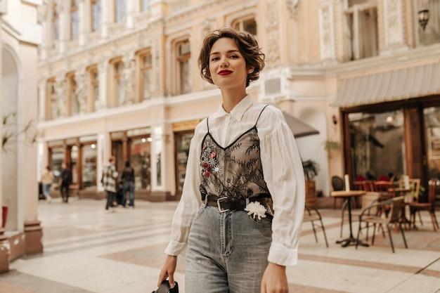 Mooie vrouw met golvend haar in spijkerbroek met riem en bloem lachend op straat. koele dame in witte blouse met kant poseren in de stad.