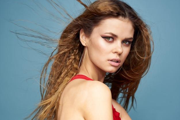 Mooie vrouw met golvend haar lichte make-up rood t-shirt levensstijl blauw model.