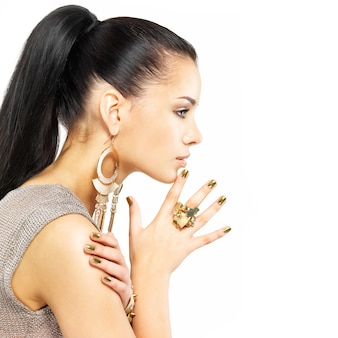 Mooie vrouw met gouden spijkers en mooie gouden die juwelen op wit worden geïsoleerd