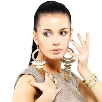 Mooie vrouw met gouden spijkers en mooie gouden juwelen die op witte muur worden geïsoleerd