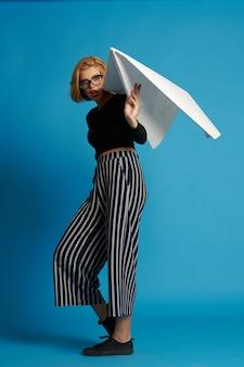 Mooie vrouw met groot papieren vliegtuigje